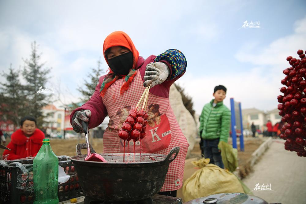 家乡临夏保留着每年闹秧歌、玩社火的风俗习惯。社火一来,人山人海。商贩们也就跟着来了。一位附近的农村大姐正在做新鲜的冰糖葫芦。