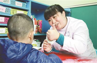 康复治疗师对自闭症儿童进行训练.