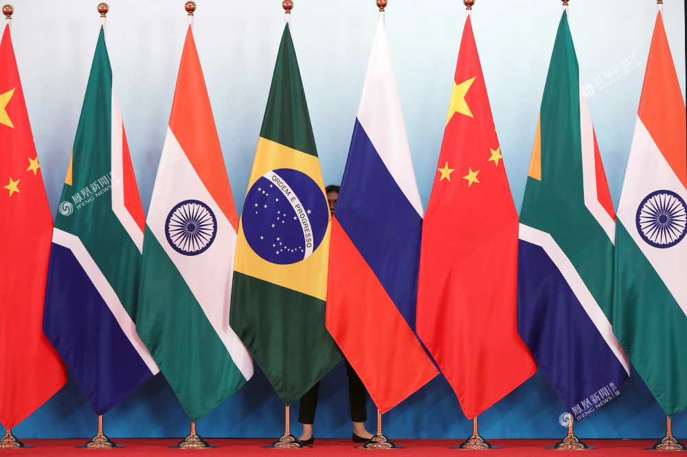 4日,厦门国际会议中心,一名工作人员站在金砖五国的国旗后面.