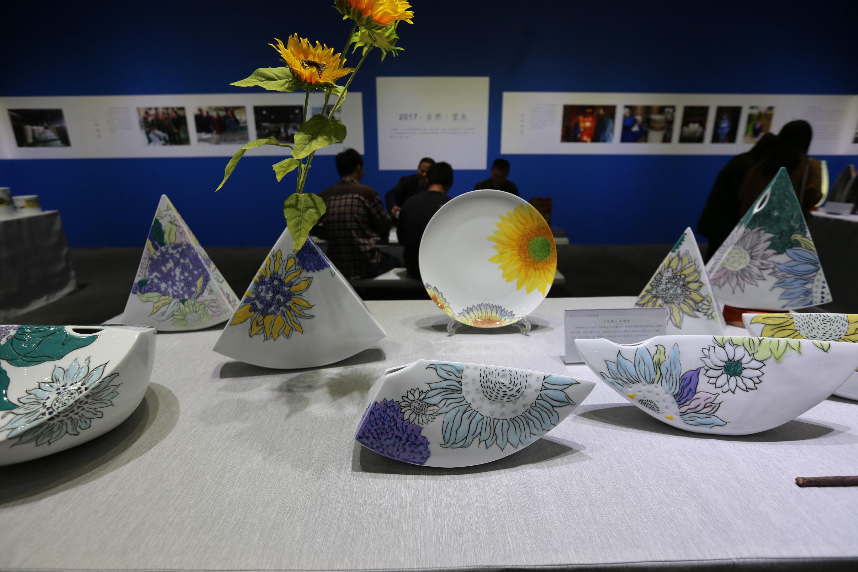向日葵主题系列陶瓷(王东摄) 据介绍,望龙向日葵主题系列陶瓷,是全手工打磨餐具,全程使用手工成型,圆形流畅、方形菱角分明,每一道线条,每一个转折都来自设计者的思维灵感,手随心动,自然、真实,开创性的造型仿佛未来陶瓷穿越而来。