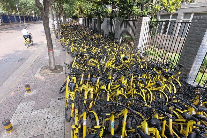堆放的共享单车,把行人逼到机动车道