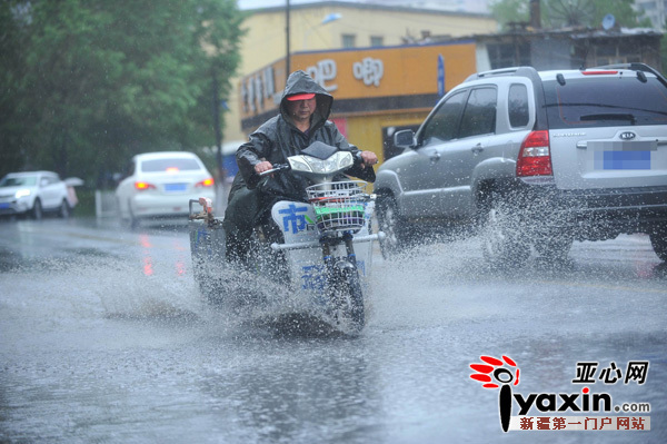 车辆经过雨水路面溅起水花.(查看高清图)