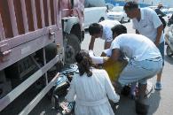 郑州街头电动车被卷大车下 小伙救3人后悄然离去