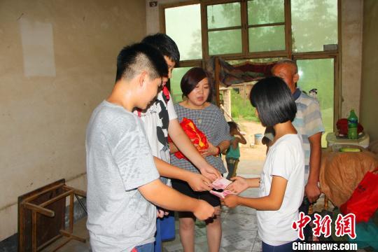 老师和学生代表将捐赠的物品交给薛思毓。 崔涛 摄
