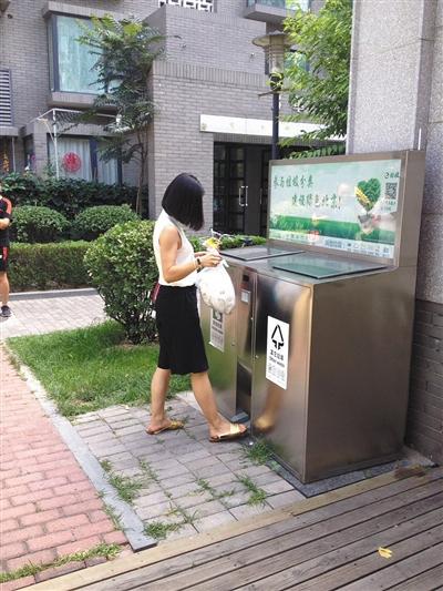 区玉廊东园小区内,一名市民正在使用智能分类垃圾桶