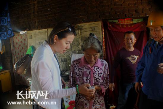 帮扶支援小组成员指导村民使用遥控智能照明灯。