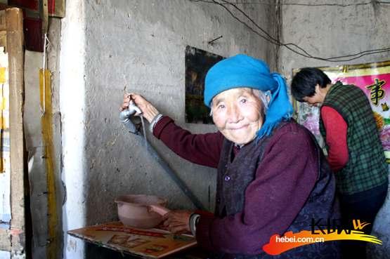 老人用上自来水,特别高兴。孟宪丛 摄