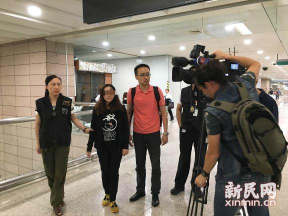 图说:国际红色通缉令出逃人员刘某(中)被上海警方押送回沪。赵立荣/摄