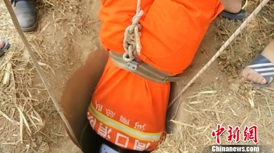 消防人员倒挂金钩营救坠井男童。 葛鑫 摄