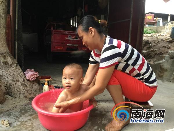 渔嫂杨丽正在用刚投入使用的海水淡化厂生产的淡水给儿子洗澡。南海网记者高鹏摄