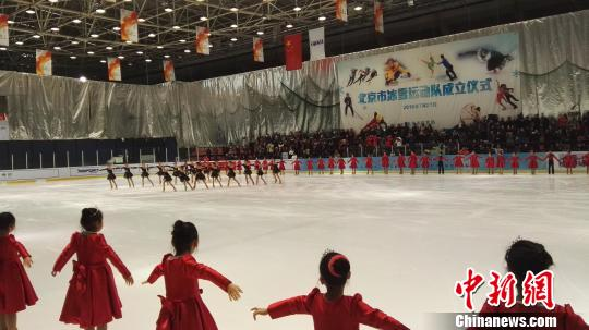 身着黑色演出服的选手正在进行花样滑冰队列滑表演. 王婧 摄图片