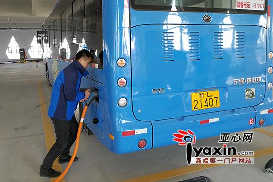 工作人员为新能源公交车充电.
