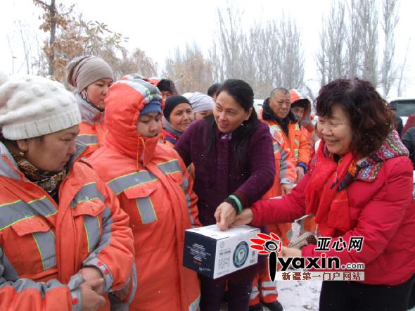 中国圣牧有机奶业有限公司总经理张籍圆(左三)向环卫工人分发牛奶.