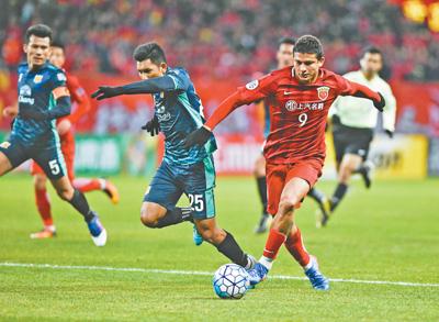 2月7日,上海上港队球员埃尔克森(前右)在比赛中与对手拼抢.