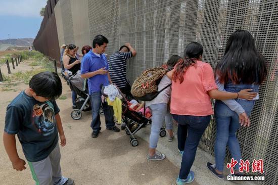 资料图美墨边境两边的亲人隔着栅栏相聚。