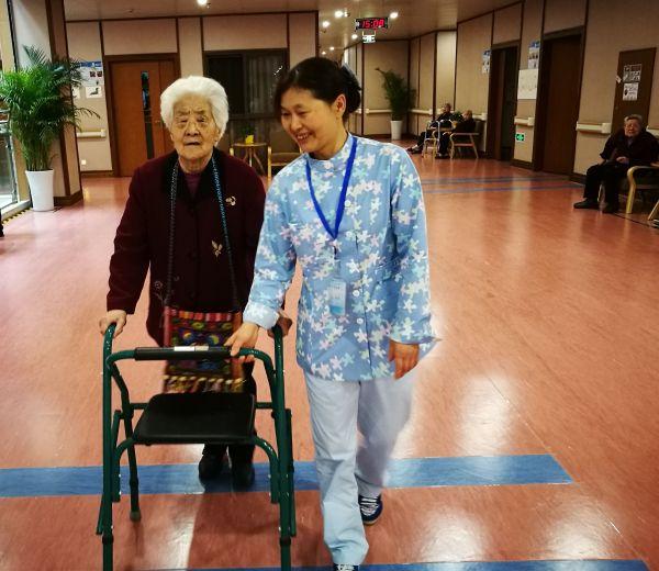 资料图片:护理员正扶持老人进行行走康复训练。新华社记者董小红摄