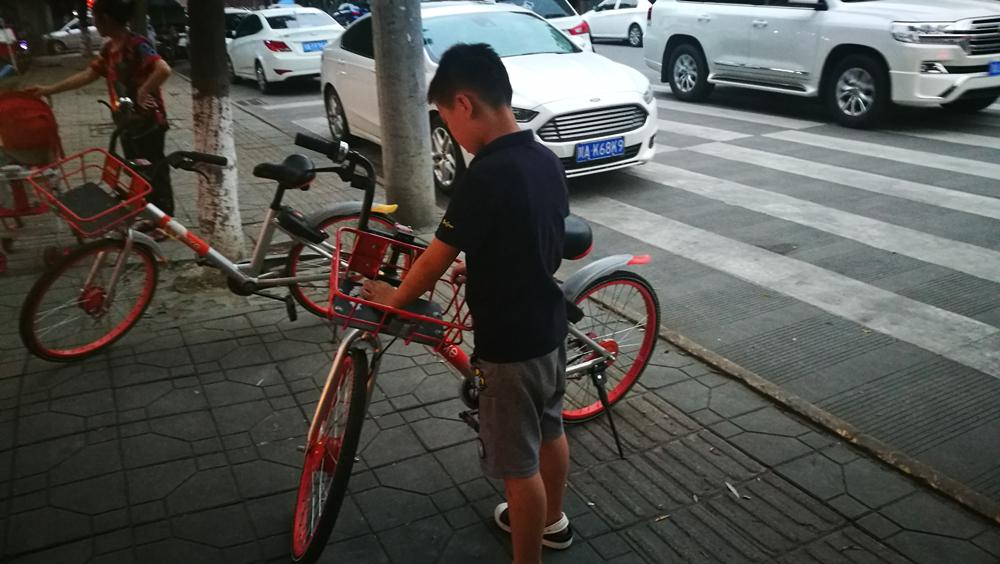 少年手撕共享单车牛皮癣广告抱怨贴的人没素质