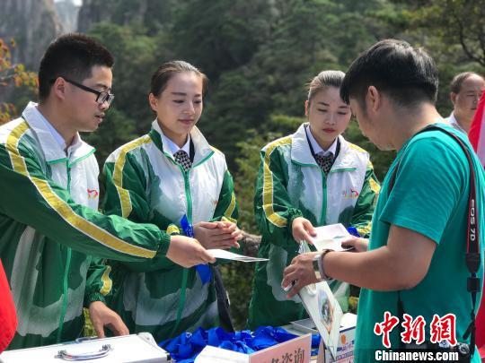 志愿者向游客发放垃圾袋和蓝丝带侯晏摄