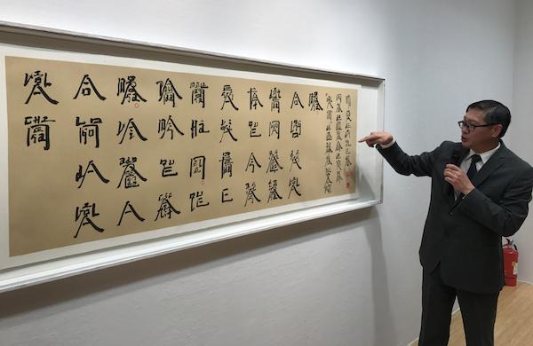 展览现场,澳门艺术博物馆馆长陈继春介绍徐冰的萄文书法作品