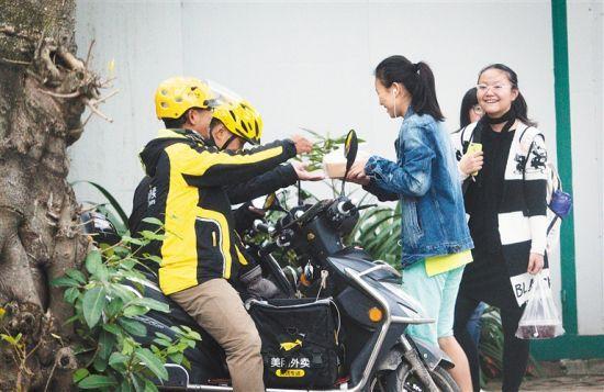 海南大学学生宿舍楼前,学生们在取外卖。 记者宋国强摄