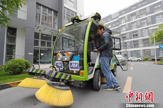 工作人员正在对无人驾驶清洁车进行程序优化调试。 殷立勤摄