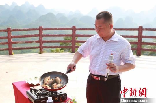 稻田鱼代言人、连南县科技和农业局局长毛监文现场煎起稻田鱼。 许青青摄