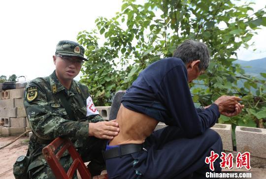 医疗分队为受灾民众巡诊看病。 胡程摄