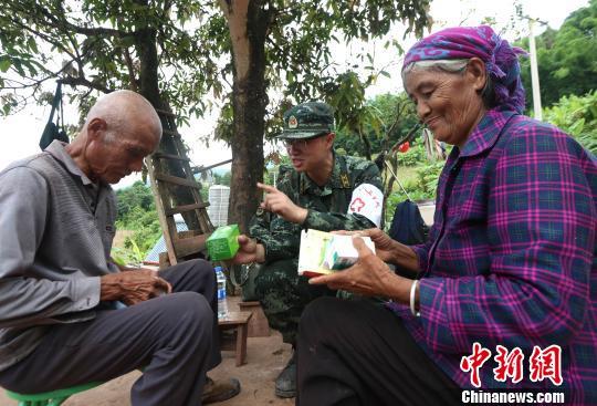 医疗分队为受灾民众巡诊看病。 任东摄