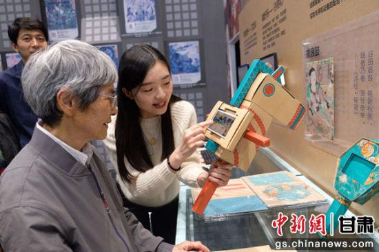 """图为敦煌研究院名誉院长樊锦诗体验""""动起来""""的敦煌壁画游戏。腾讯互动娱乐供图"""