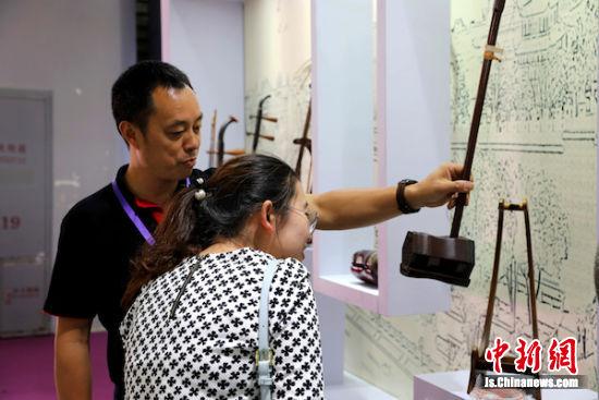 厂家负责人为参观者介绍二胡产品。