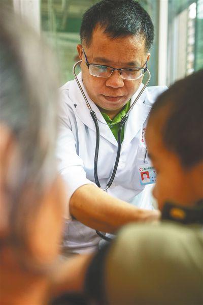 全科医生黄壮锦在为患者诊治。海南日报记者袁琛摄