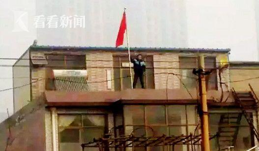 网上流传的贾敬龙家被拆时照片,贾敬龙举着红旗站在楼上。