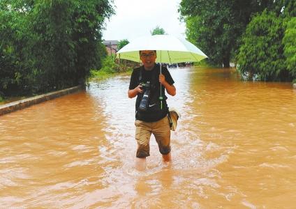 张磊在洪水中采访。资料图片