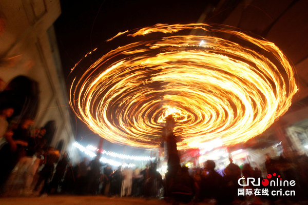 當地時間2016年10月9日,伊拉克民眾慶祝阿舒拉節,夜晚街頭舉行火炬表演,場面異常精彩。圖片來源:視覺中國